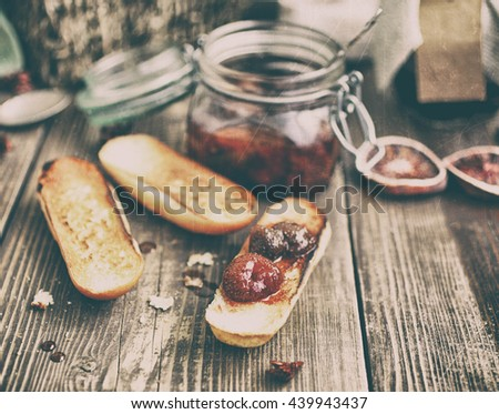 Strawberry jam and toasts on a wooden table. Top view. Vintage toning