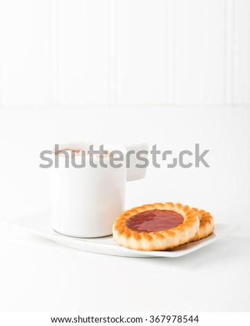 Strawberry jam filled cookies served with hot chocolate. - stock photo