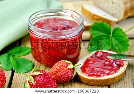 Strawberry jam in a glass jar, bread, strawberry with leaves, napkin, knife on background wooden plank - stock photo