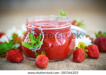 strawberry jam in a glass jar with strawberries on a table