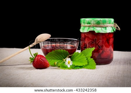 Strawberry jam in jar with spoon and fresh berries on linen and black background