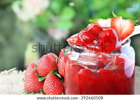 Strawberry jam on sackcloth with green blur background