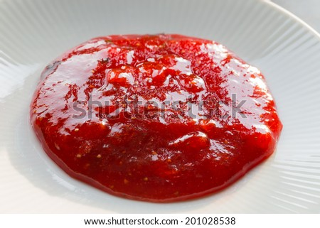 Strawberry jam sample on a white plate.