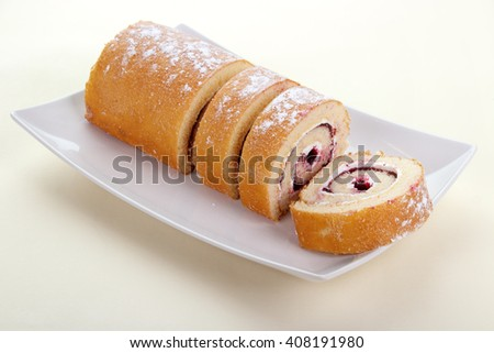 Strawberry jam swiss roll dessert on square plate , disposable paper tablecloth background  - stock photo