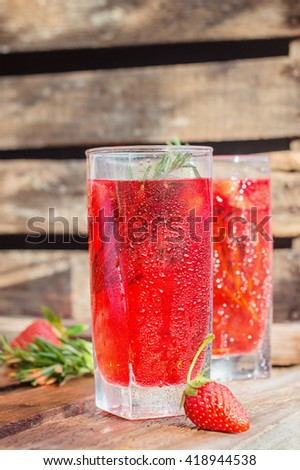 strawberry lemonade in a clear glass Cup on wood background - stock photo
