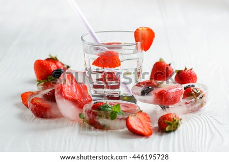 Strawberry lemonade with ice in glass on wooden background