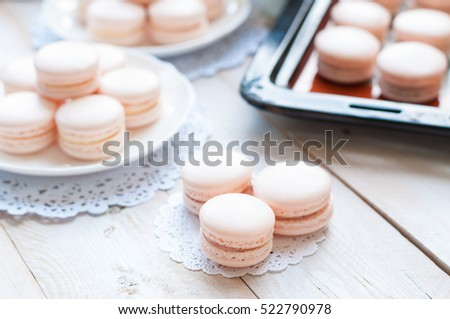 Strawberry macarons with a cup of tea on white wooden background