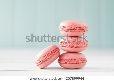 Strawberry macaroons (aka macarons) on a white wooden table with a robin egg blue background. Vintage Style. - stock photo