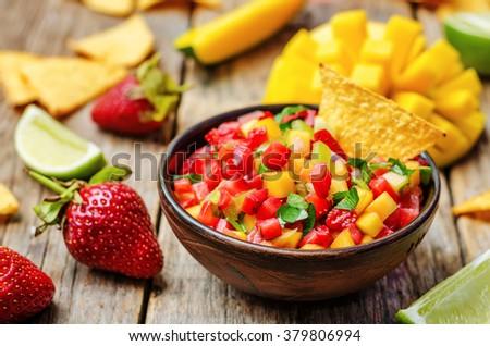 strawberry mango pepper salsa on a dark wood background. toning. selective focus  - stock photo