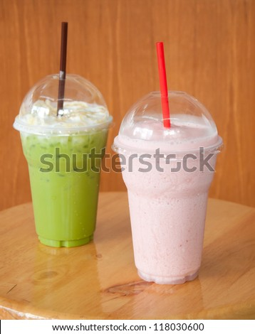 strawberry milkshake and iced green tea on wood table - stock photo