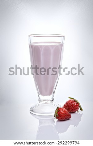 Strawberry milkshake in a tall glass with fresh srtrawberry - stock photo