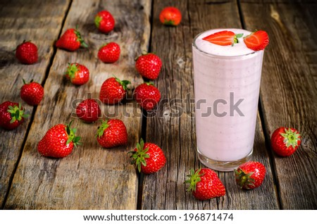 strawberry milkshake with strawberry on the dark wood background. toning. selective focus on the strawberries in the glass - stock photo