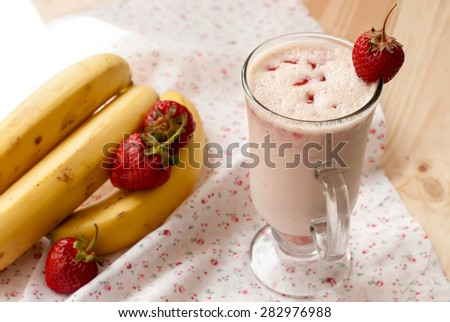 strawberry milkshakes in tall glasses and bowl of strawberries