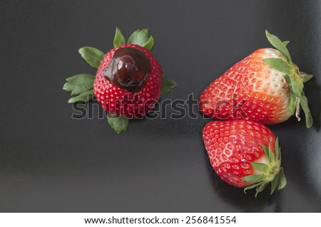 Strawberry on a black plate, with chocolate - stock photo