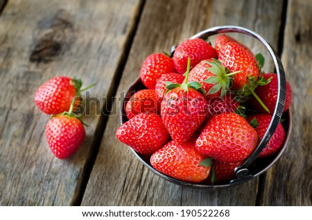 strawberry on a dark wood background. selective focus on strawberries in the bowl - stock photo