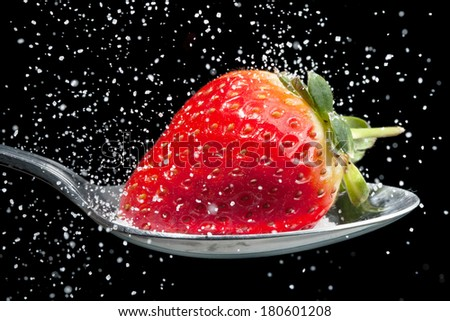 Strawberry on a spoon with sugar pouring over it, frozen with high speed photography - stock photo