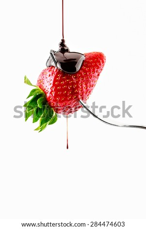 Strawberry on fork falling liquid chocolate on a white background.Vertical image