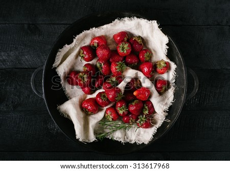Strawberry on light textiles in a bowl on a black wooden background - stock photo