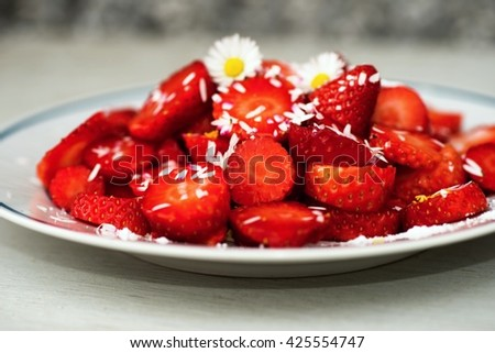 Strawberry on white plate, flower daisy, blurred background