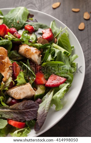 Strawberry Orange Honey Balsamic Salad on spring baby greens and spinach macro shot