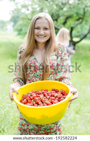 Strawberry picking: image of gathering strawberry on bright summer day green garden outdoors background happy blond young pretty woman teen girl having fun smiling & looking at camera portrait - stock photo