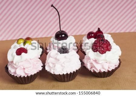 Strawberry pink cupcakes with whipped cream and fruit on top - stock photo