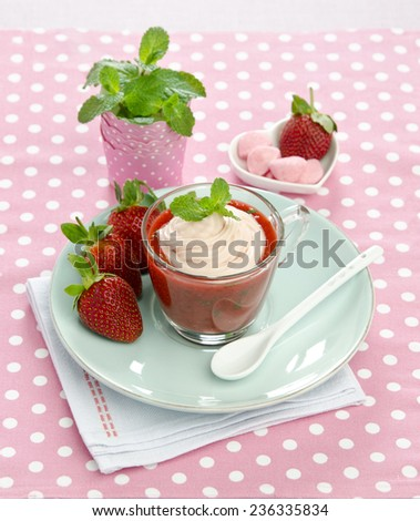 strawberry puree with mint and pink cream in a glass cup on a blue plate with strawberries on pink background - stock photo