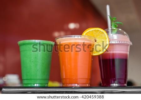 Strawberry, raspberry, orange, kiwi and avocado smoothies in plastic recyclable cups - stock photo