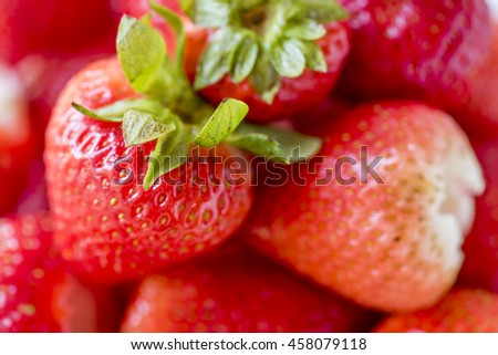 Strawberry: Red Strawberry, red close up strawberries with selective focus on a strawberry with many strawberries in the background for food or fruit close up background or strawberry texture. - stock photo