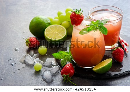 Strawberry refreshing juicy summer drink with ice cubes, lime, mint. Home-made lemonade, lime water - stock photo