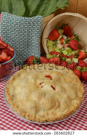 Strawberry-Rhubarb Pie on a country table with strawberries and rhubard and a red and white checkered table cloth