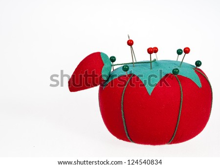 Strawberry shaped pincushion with pins in it
