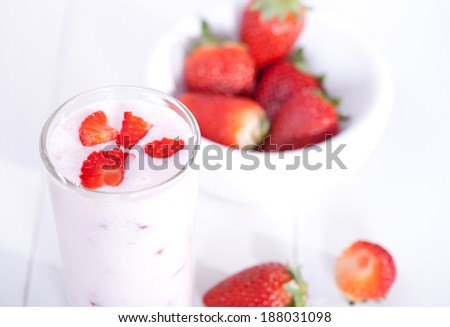 Strawberry smoothie and bowl of strawberry on a wooden table