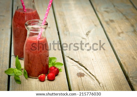Strawberry smoothie freshly made in a jar with a lined straw on rustic wood - stock photo