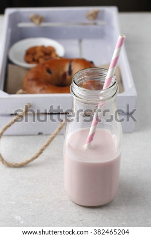 Strawberry smoothie in a glass bottle. Blueberry bagel and nuts in the background