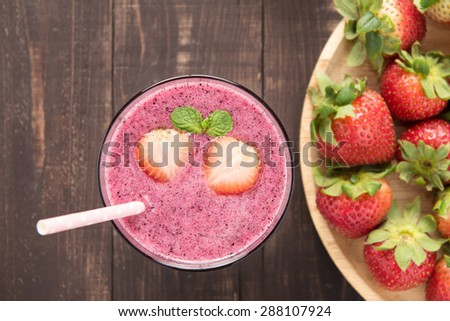 Strawberry smoothie in glass and fresh strawberries on wooden background. - stock photo