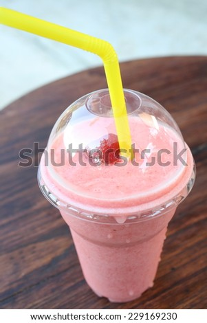strawberry smoothie in plastic glass on wooden table. feeling fresh with iced drink - stock photo