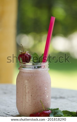 Strawberry smoothie made with fresh strawberries and yogurt, garnished with mint.