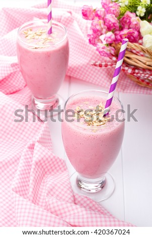 Strawberry smoothie with oatmeal on white wooden table and pink table cloth - stock photo
