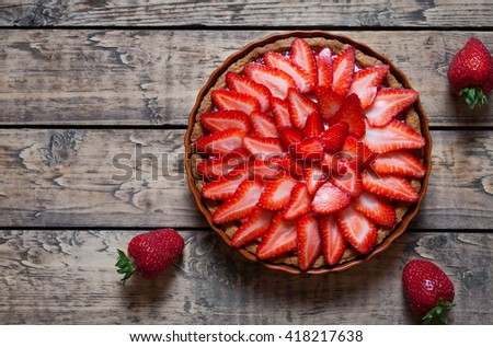 Strawberry tart with cream traditional summer sweet pastry fruit dessert on vintage wooden table background - stock photo
