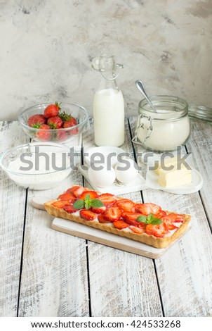 Strawberry tart with custard. Tart and ingredients for tart - milk, sugar,butter, flour, eggs and strawberry. Homemade pie with fresh strawberry - stock photo