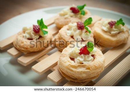 Strawberry Tart with Fresh Cream in Puff Pastry on wooden mat - stock photo