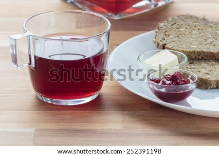 Strawberry tea, strawberry jam, butter and rye bread for breakfast - stock photo