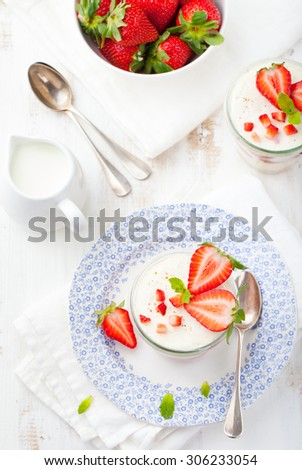 Strawberry tiramisu, trifle, custard dessert  in a glass with fresh strawberry and mint leaves on a white wooden background - stock photo