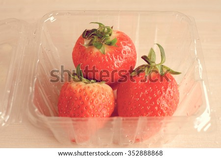 Strawberry with package plastic, vintage tone - stock photo