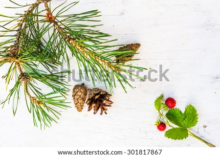 Strawberry with pine branches with cones on old wooden table