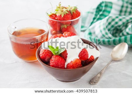 strawberry with sour cream in a bowl on a table, selective focus