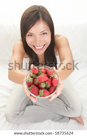 Strawberry woman showing fresh strawberries. Top view of beautiful female model sitting in bed with copy space around. - stock photo