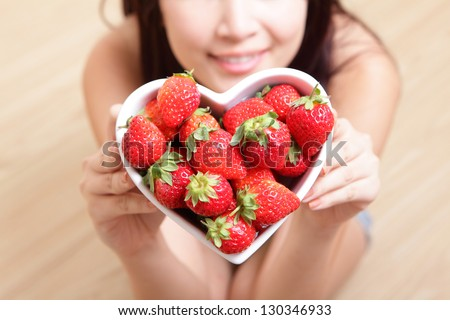 strawberry - Woman smiling with strawberry on wooden floor background, focus on fruit, asian beauty model