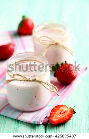 Strawberry yogurt in glass on a mint wooden table